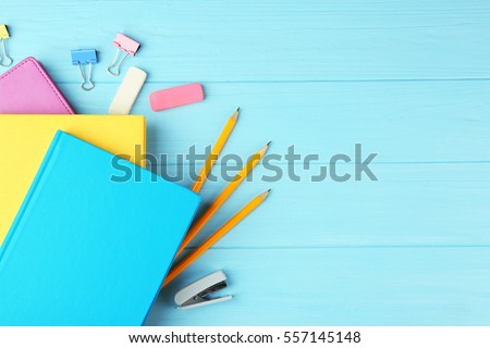 Colorful notebooks and office supplies on wooden background stock photo