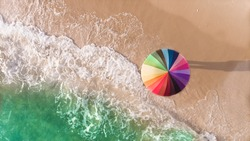Colorful of umbrella on the beach and foam of sea wave from top eye view photo in outdoor sunlight lighting.