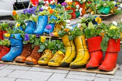 Colorful old boots used as flower pots.
