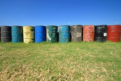 Colorful old oil drums on the grass