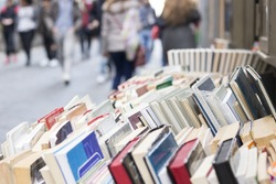 Colorful old second hand books display on a stand, in a street of Naples, Italy. Blurred people  doing shopping in background. Horizontal