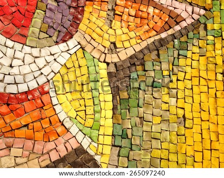 Colorful old stone mosaic on the wall, bright tiles, floral theme