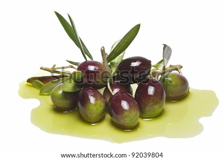 Colorful olives with leaves covered on olive oil and isolated over a white background.
