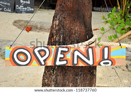 Colorful open sign on the beach