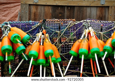 Colorful orange and green lobster floats hanging off purple lobster traps and wood barn