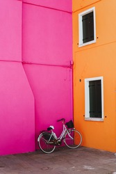 Colorful orange and pink houses next to a white bike. Artsy Colors in Murano, Venice, Italy.