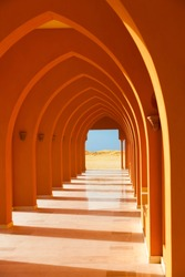 Colorful orange arched hallway passage with columns leading to a desert on a sunny day.