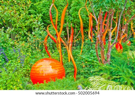 Colorful orange glass art in natural garden setting at the Chihuly Gardens and Glass Exhibit, Seattle, Washington