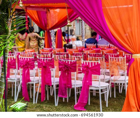 Colorful outdoor lawn tent and garden setting for Indian pre-wedding ceremony.  Vibrant pink and orange silk fabric curtains and bows on white chairs. Guests in background.
