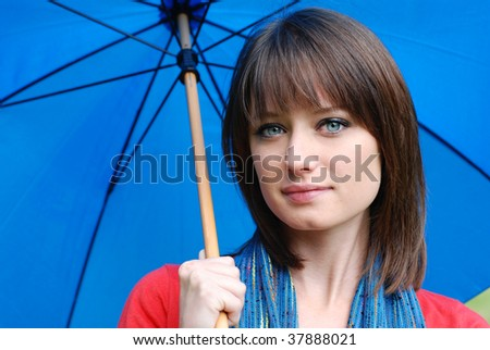 Colorful outdoor portrait of beautiful brunette with blue umbrella.  Close-up with shallow dof.
