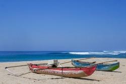 Colorful outrigger fishing boats on Wanokaka beach, Lamboya, Sumba island, East Nusa Tenggara, Indonesia