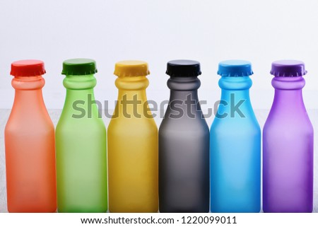 Colorful paint. Bottles with colorful dry pigments on white wooden background. Rainbow colors: choosing the right color. Colored beverages concept #1220099011