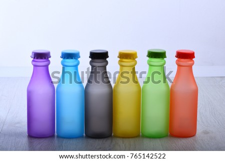 Colorful paint. Bottles with colorful dry pigments on white wooden background. Rainbow colors: choosing the right color. Colored beverages concept #765142522
