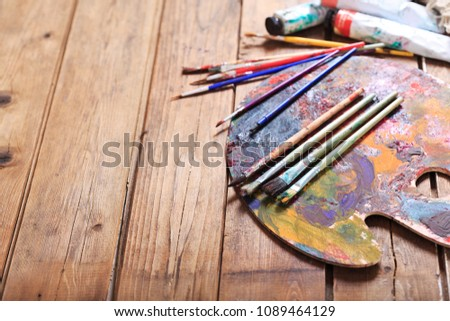 colorful paint brushes on a palette #1089464129