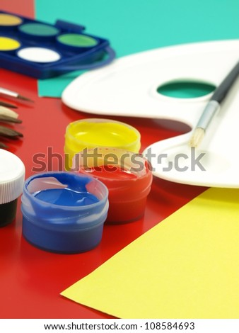 Colorful paint in small jars and palette,closeup