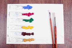Colorful paint strokes with brush and tubes of paint on white sheet of paper on wooden table background