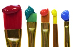 Colorful paintbrushes are placed vertically next to each other and each has color at the tip, against a white background