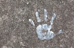 Colorful painted childs hand print on the concrete floor symbol. Small, little child's handprint reflected on the ground with paint. Arts, crafts, creativity, development psychology abstract concept