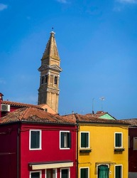 Colorful painted front houses in Burano whit the leaning bell tower of San Martino church in the background, travel background, Italy