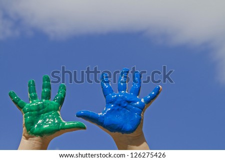 Colorful painted hands against blue sky