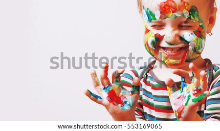 Colorful painted hands in a beautiful young girl #553169065
