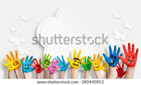 colorful painted hands in front of a decorated wall with a flower and butterflies