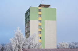 Colorful painted old panel concrete residential block. Socialist architecture. Residential building and white frozen trees on blue sky background in winter. Copy space.