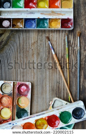 Colorful paints and brushes arranged as a frame on wooden table