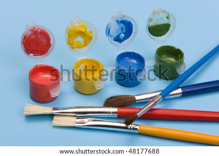 Colorful paints and brushes on a blue background