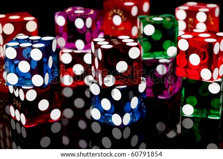Colorful pairs of casino gaming/gambling dice isolated on a black background with reflection.