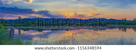Colorful panoramic photo of a sunset behind a pond in Boulder, Colorado. #1156348594