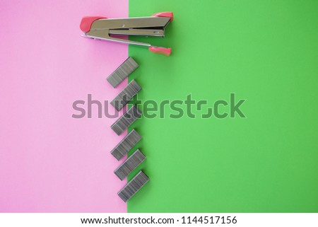 Colorful paper and paper stapler with copy space. stationery concept for office desk.