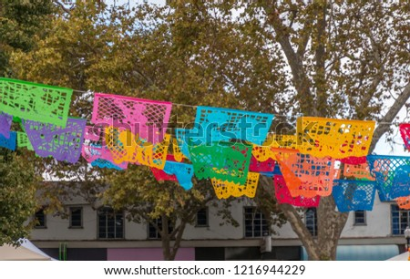 Colorful paper cutouts hang from lines to decorate the Day of the Dead celebration. The cut outs are blue, green, yellow and red. Trees and buildings are behind the cut outs. #1216944229