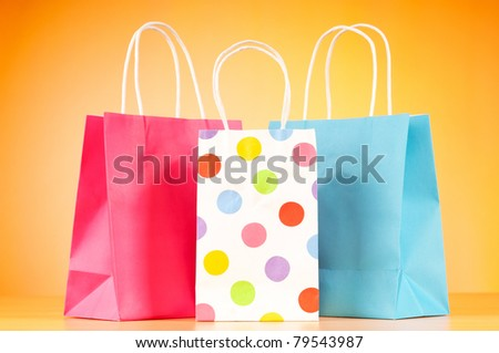 Colorful paper shopping bags against gradient background - stock photo