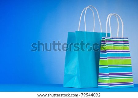 Colorful paper shopping bags against gradient background