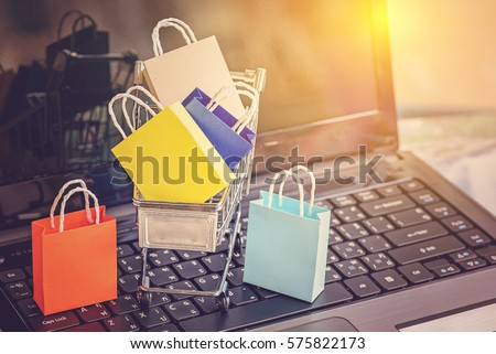 Colorful paper shopping bags in a trolley. Ideas about online shopping addiction. A shopping addict is someone who shops compulsively and who may feel like they have no control over their behavior.