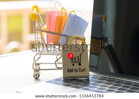 Colorful paper shopping bags in trolley and bag with cart symbol on laptop keyboard. Consumer buy products directly anywhere anytime from seller using website. Online shopping and e-commerce concept.