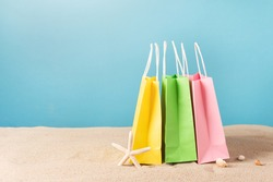 Colorful paper shopping bags on beach sand. Summer sale concept.
