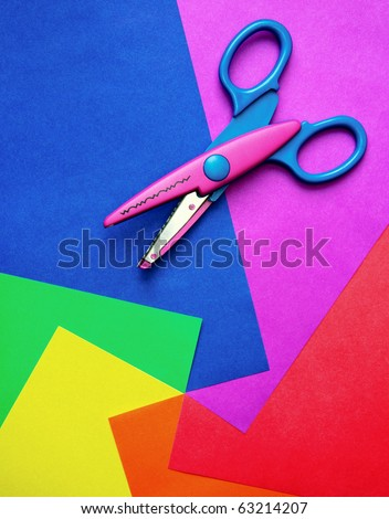 Colorful paper with child's scissors
