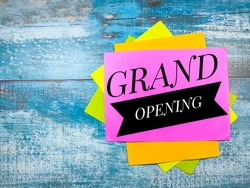 Colorful paper with text GRAND OPENING on blue wooden background.