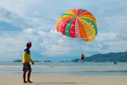 Colorful Para sailing the most popular water sport activity on the beach. It combines the thrills of acceleration and altitude with the scenic views of Andaman Sea