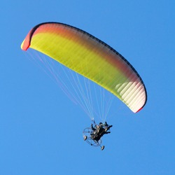 Colorful paraglider on blue bright sky