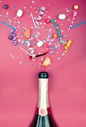 Colorful party attributes fly out from botle of champagne wine. on a red background. Flat lie. Celebrate concept. High resolution photo.