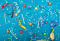 Colorful party attributes with streamers, confetti and horns over BLUE background. Flat lie. High resolution photo.