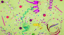 Colorful party attributes with streamers, confetti and horns over GREEN background. Flat lie. High resolution photo.