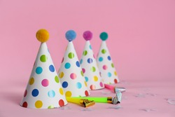 Colorful party hats with fluffy balls and blowers on pink background