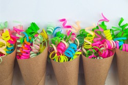 Colorful party streamer in bags over white background. Copy space