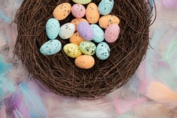 Colorful pastel colored easter eggs in bird's nest top view with bright feasthers top view, April, Easter Holliday, Religion and spring concept background close up