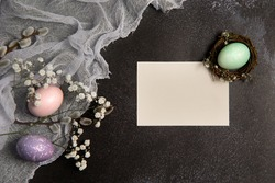 Colorful pastel easter eggs in a nest on a dark background with space for caption