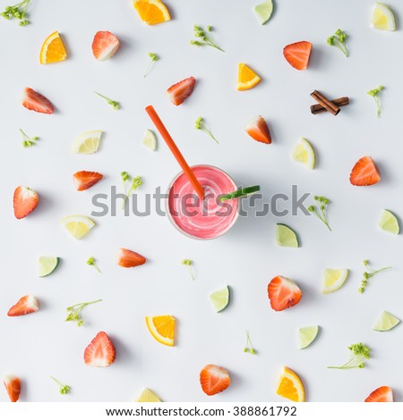 Colorful pattern made of citrus fruits, leaves and strawberries with smoothie.
